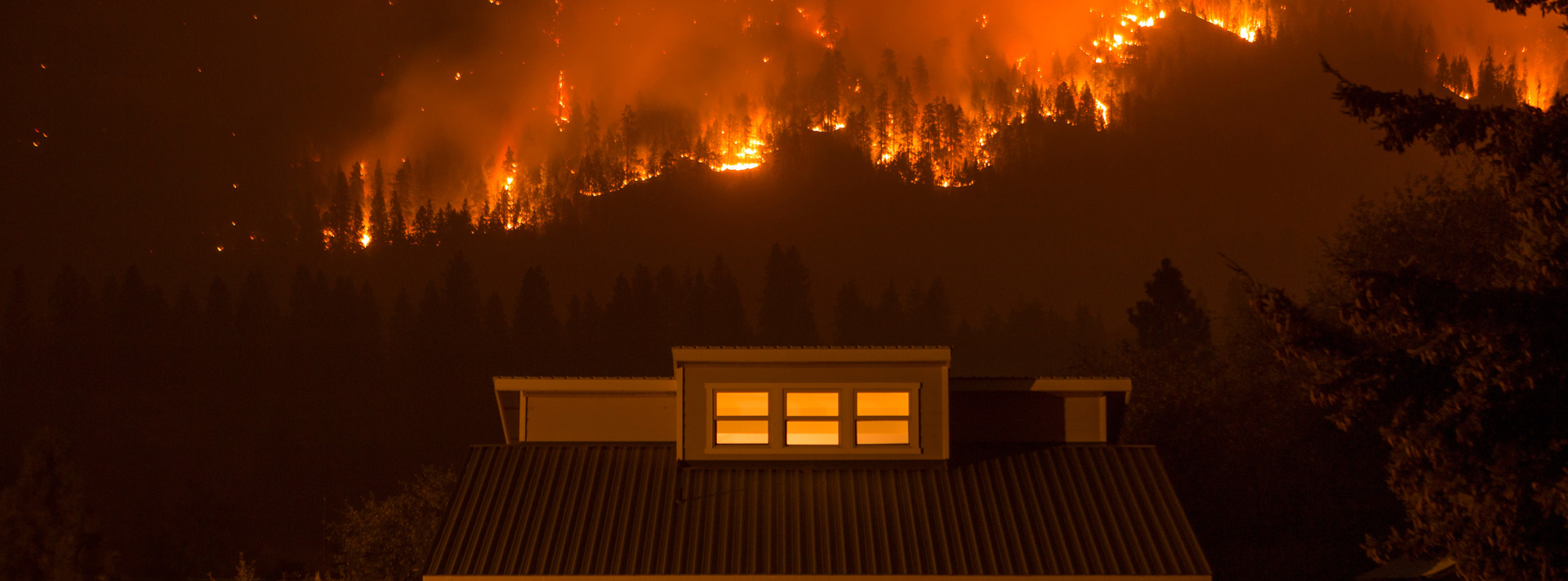 Forest fire behind a house