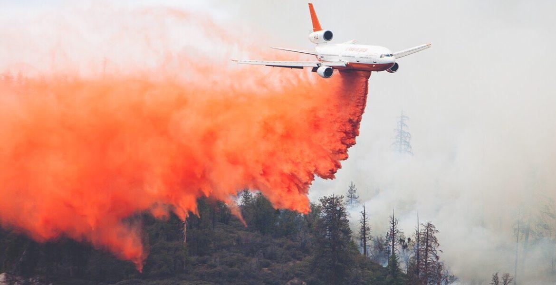 Small plane dropping fire retardant onto a wildfire.