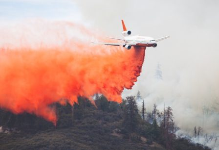 Small plane dropping fire retardant onto a wildfire.