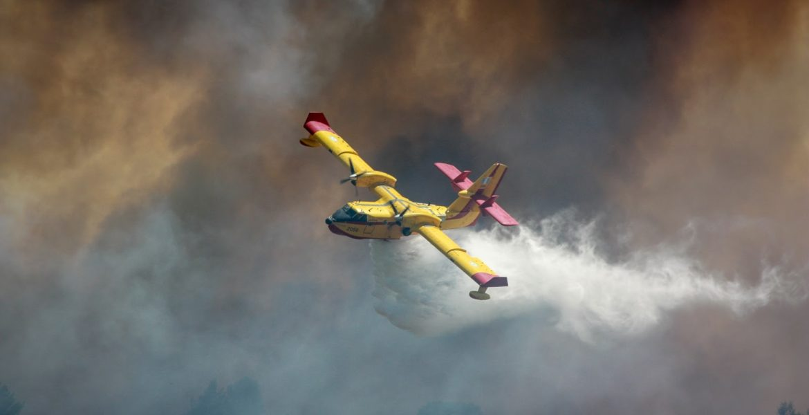 fire suppression plane flying through thick smoke.